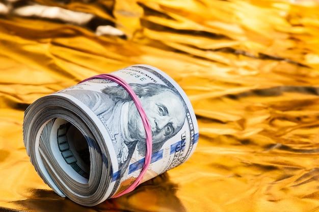 Eine rolle von dollar liegt auf einem goldenen hintergrund.