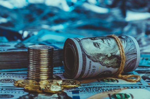 Eine rolle von dollar mit münzen auf dem hintergrund von zerstreuten hundert dollarscheinen im blauen licht.