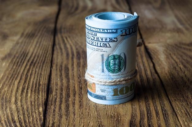 Eine rolle von dollar steht auf einer hölzernen strukturierten tabelle.