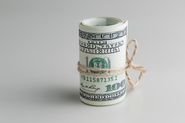 Eine rolle von hundert dollarscheinen gebunden mit einem seil auf einem grauen hintergrund. seitenansicht.