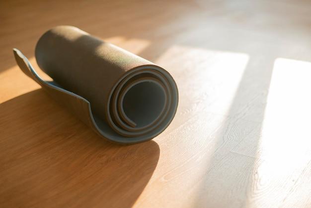 Eine rolle yogamatte auf dem holzboden, training im fitnessstudio, sportgeräte