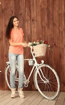 Eine romantische junge frau, die mit ihrem fahrrad und einem korb von wildblumen in die kamera schaut. sommer.