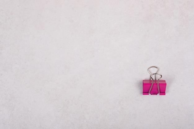 Eine rosa büroklammer auf weißem hintergrund