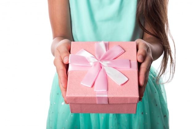 Eine rosa geschenkbox mit einem bandbogen in den händen des mädchens, die ein geschenk geben