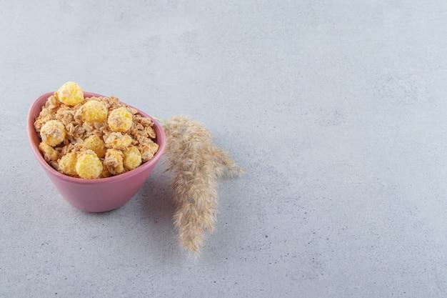 Eine rosa tiefe schüssel mit köstlichem gesundem getreide auf grauem hintergrund. foto in hoher qualität