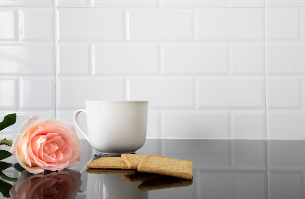 Eine rose, stücke biskuit und eine tasse kaffee