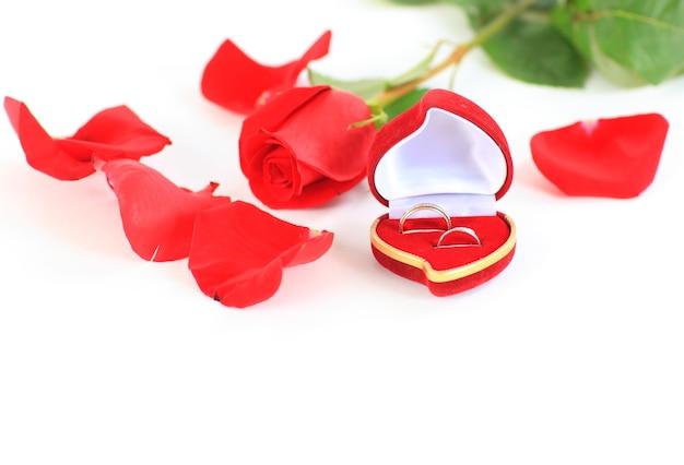 Eine rose und eine schachtel mit ringen