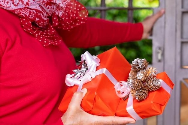 Eine rot gekleidete frau hält zwei weihnachtspakete mit schleifen und dekoration vor dem tor des hauses