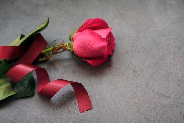 Eine rot-rosa rose auf einer dunkelgrauen oberfläche mit burgunderfarbenem band