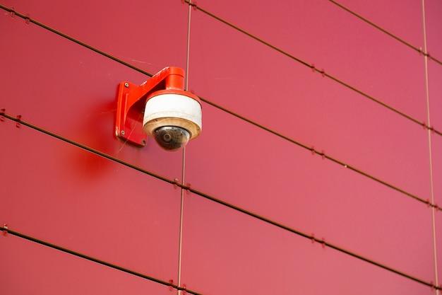 Eine rot-weiße überwachungskamera auf roter metallwand