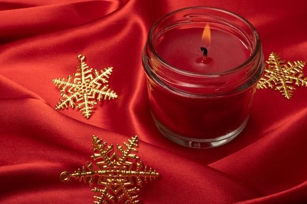 Eine rote duftkerze mit weihnachtssternverzierungen auf einem leuchtend roten seidentuchhintergrund.
