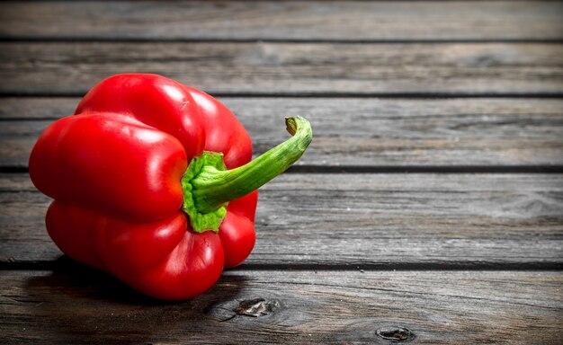 Eine rote paprika auf holztisch