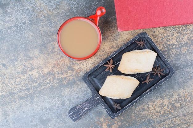 Eine rote tasse aromakaffee mit buch und keksen. foto in hoher qualität
