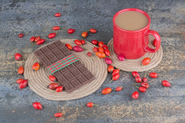 Eine rote tasse getränk mit schokolade und hagebutten auf marmorhintergrund. foto in hoher qualität