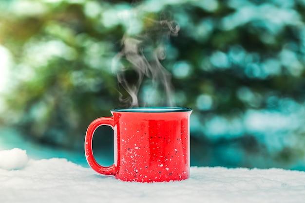 Eine rote tasse mit einem heißen wintergetränk (glühwein, kakao, kaffee, tee) vor dem hintergrund eines winterwaldes und des schnees. winterstimmung und komfort.