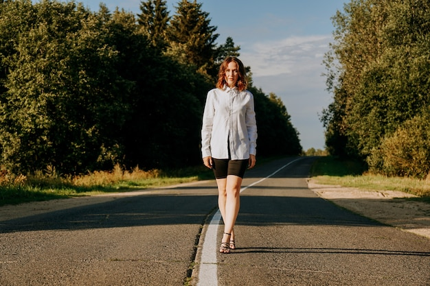 Eine rothaarige frau in einem weißen hemd geht an einem sonnigen sommertag die straße entlang durch den wald. ein ausflug aus der stadt. Premium Fotos