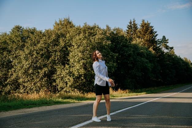 Eine rothaarige frau in einem weißen hemd geht an einem sonnigen sommertag die straße entlang durch den wald. ein ausflug aus der stadt.