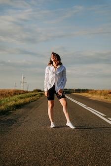 Eine rothaarige frau in einem weißen hemd geht an einem sonnigen sommertag die straße entlang zwischen den feldern. ein ausflug aus der stadt. vertikales foto