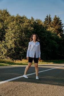 Eine rothaarige frau in einem weißen hemd geht die straße entlang durch den wald