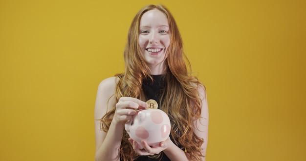Eine rothaarige junge frau mit einer rosafarbenen schwein-bankspardose für bankspareinlagen