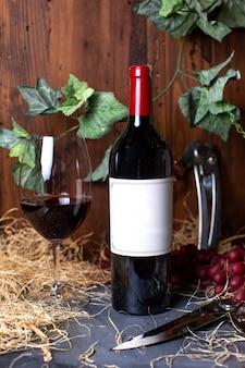 Eine rotweinflasche rotwein der vorderansicht zusammen mit den roten beeren und den grünen blättern, die auf dem grauen schreibtischalkohol-weingutgetränk isoliert werden