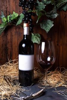 Eine rotweinflasche rotwein der vorderansicht zusammen mit schwarzen trauben und grünen blättern lokalisiert auf dem grauen schreibtischalkohol-weingutgetränk