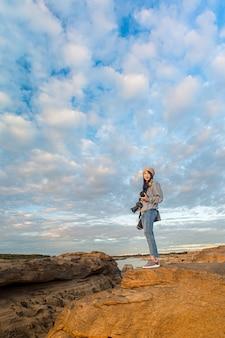 Eine rucksacktouristin steht auf der felsgrube des grand canyon bei sonnenuntergang bei dreitausend wellen