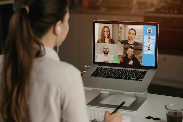 Eine rückansicht einer geschäftsfrau zu hause in einer videokonferenz mit ihren kollegen während eines online-meetings. partner in einem videoanruf. multiethnisches business-team, das eine diskussion in einem online-meeting führt.