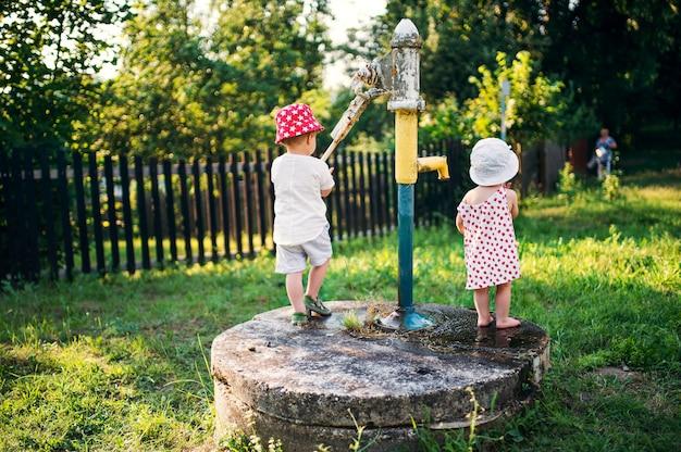 Eine rückansicht von kleinkindern, die im sommer draußen im garten stehen.