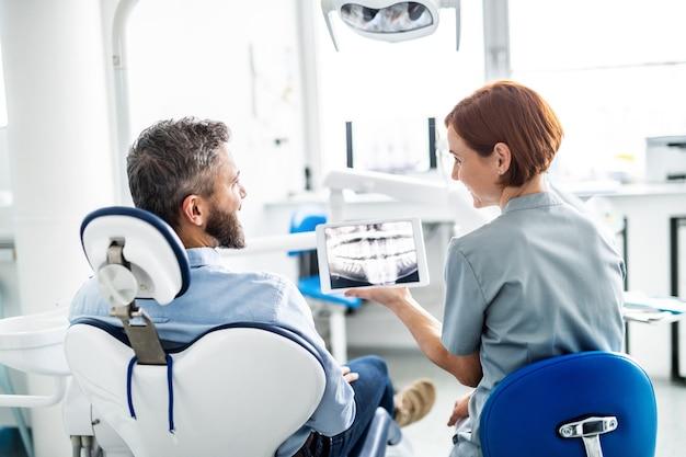 Eine rückansicht von mann und zahnarzt in der zahnchirurgie, jährliche kontrolle.