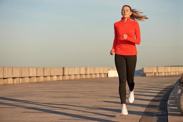 Eine rüttelnde frau im roten laufenden hemd und in den schwarzen leggins auf der straße bei sonnenaufgang. laufen auf betonkai