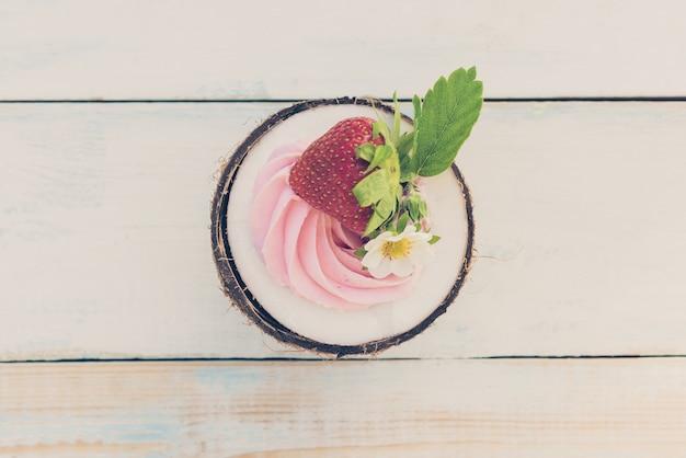 Eine runde halbe kokosnuss mit erdbeeren und frischkäse auf einem holztisch. biolebensmittelkonzept. getöntes bild, draufsicht