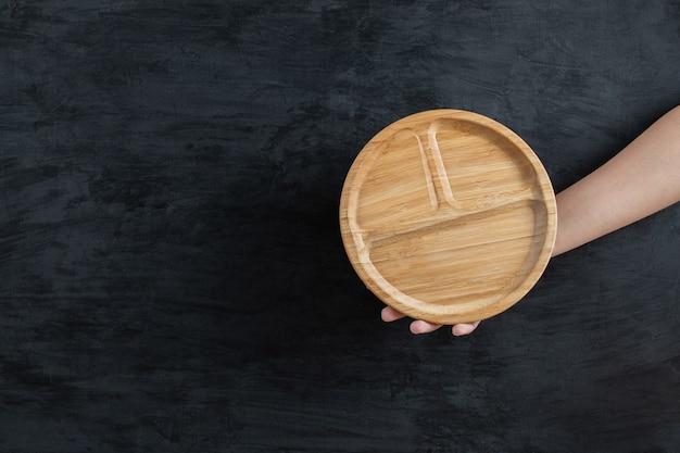 Eine runde holzplatte in der hand halten