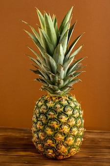 Eine saftige milde exotische ananas der vorderansicht lokalisiert auf dem braunen hölzernen schreibtisch tropische frucht saftig
