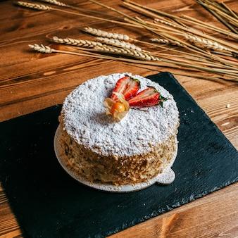 Eine sahne-torte der vorderansicht, die mit der köstlichen geburtstagstorte der geschnittenen erdbeeren innerhalb des weißen geburtstags der süßigkeit der weißen süßwaren auf dem braunen hintergrund verziert wird