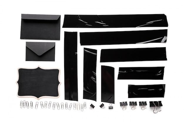 Eine sammlung benutzter schwarzer isolierbandstücke mit briefpapierwerkzeugen