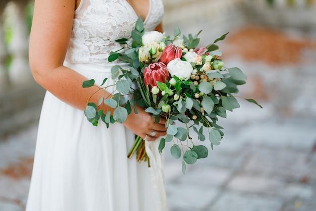 Eine sanfte braut hält in ihren händen einen ungewöhnlichen hochzeitsstrauß aus weißen pfingstrosen, rosen, proteas und