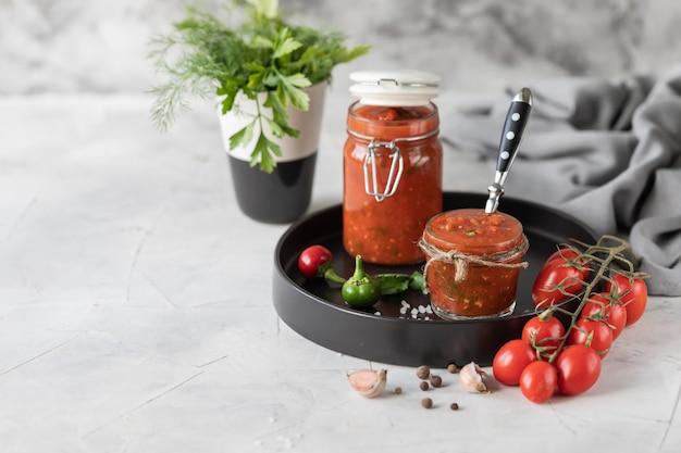 Eine sauce aus frischen roten tomaten in einem glas auf einem schwarzen teller. zweig frische kirschtomaten, knoblauch, paprika, dill und petersilie auf einem weißen tisch. eine dose hausgemachten ketchup