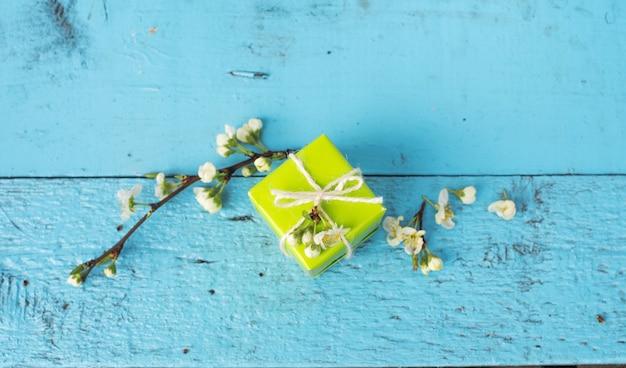 Eine schachtel der hellgrünen farbe auf einem hölzernen blauen hintergrund, frühlingsblumen. draufsicht.