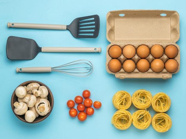 Eine schachtel eier, eine schüssel pilze, nudeln, tomaten und kochutensilien. zutaten für die herstellung von nudeln.