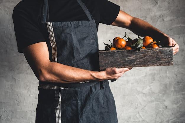 Eine schachtel mandarine in den männlichen händen auf einem grauen hintergrund. bauer, öko-früchte, essen. pnov2019