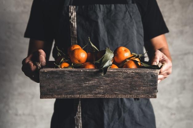 Eine schachtel mandarine in männlichen händen auf einem grau