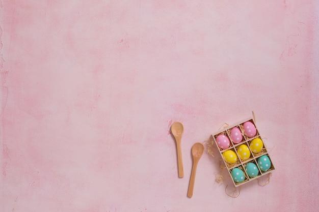 Eine schachtel mit bunten ostereiern auf rosa hintergrund
