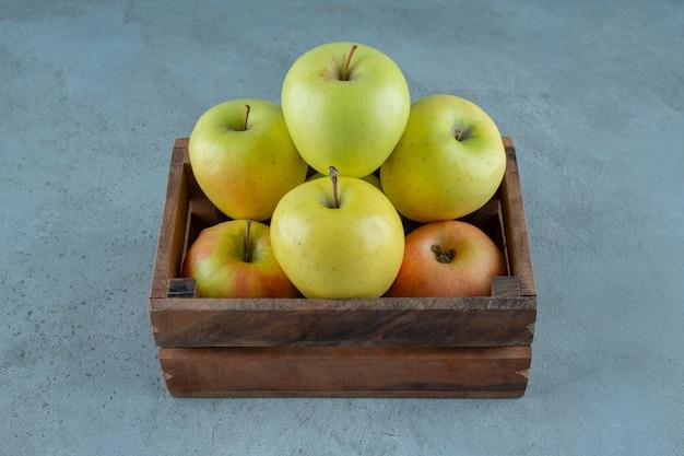 Eine schachtel mit frischen äpfeln auf dem marmorhintergrund. foto in hoher qualität
