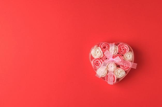 Eine schachtel mit rosenknospen, gebunden mit einem band auf einem leuchtend roten hintergrund. das konzept der liebe.