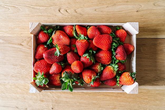Eine schachtel obst gefüllt mit erdbeeren von oben auf einem holztisch