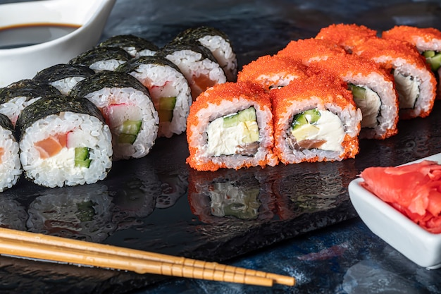 Eine schachtel sushi nigiri, uramaki, kalifornien, philadelphia, auf einer schwarzen steinplatte. sushi-menü in einer weißen transportbox auf einem hölzernen hintergrund.