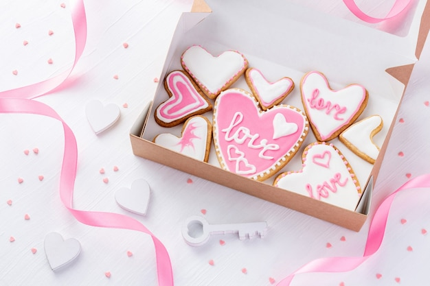 Eine schachtel voller herzförmiger kekse mit glasierter wortliebe nahe dem schlüssel auf weißem tisch für valentinstag