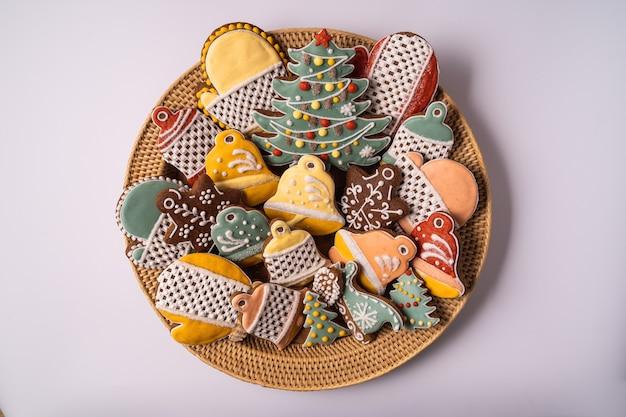 Eine schachtel weihnachtslebkuchen und dekorationen auf braunem holzhintergrund, flach gelegen.