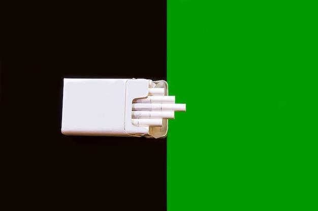 Eine schachtel zigaretten auf dunklem hintergrund neben grünem hintergrund